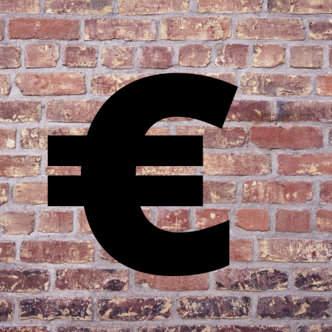 a large black euro sign against a brick wall backdrop