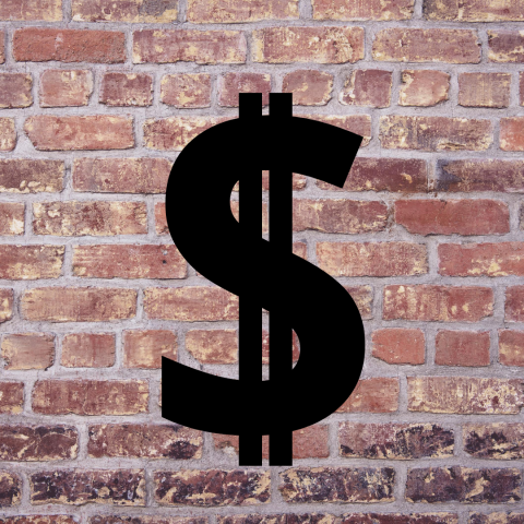 a large black dollar sign against a brick wall backdrop
