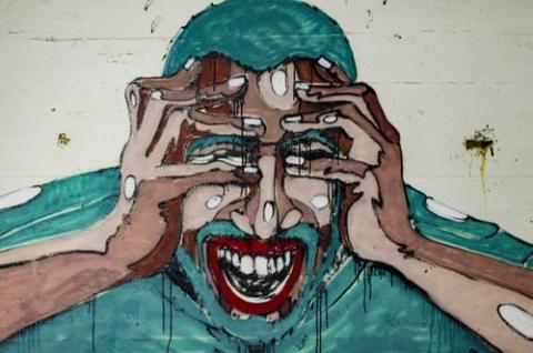 Graffiti style painting - a person holding their head in their hands - their face has an expression of confused anger