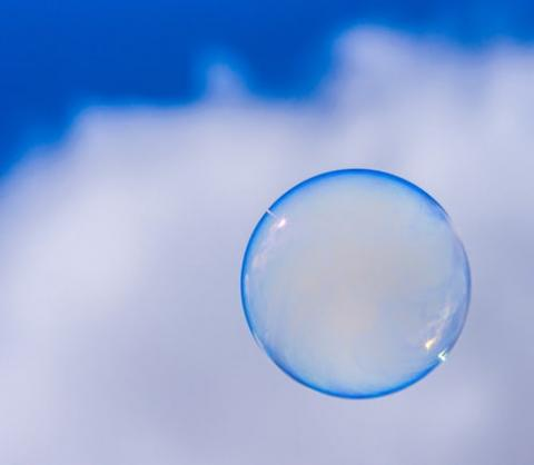 A bright blue bubble floats in front of a white cloud