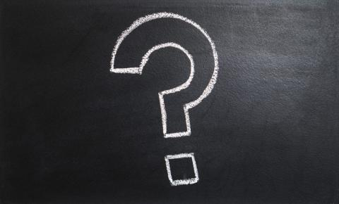 a large question mark in white chalk on a blackboard
