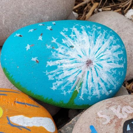 pebbles, the top one is painted to show dandelion seeds blwing away against a blue sky
